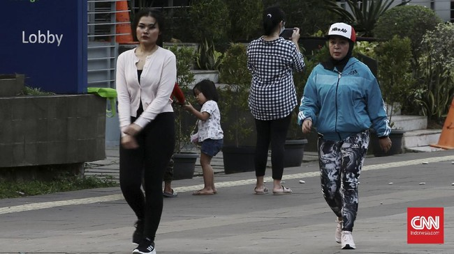 Warga Jakarta menunggu waktu berbuka puasa dengan berbagai macam aktivitas di sekitar Jalan Sudirman, Jakarta Pusat.