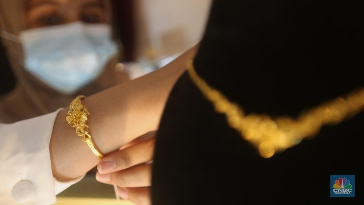 Pegawai merapikan emas batangan di Galeri 24 Pegadaian, Jakarta, Kamis (22/4/2021). Harga emas batangan yang dijual Pegadaian mengalami penurunan nyaris di semua jenis dan ukuran /satuan.  (CNBC Indonesia/Tri Susilo)