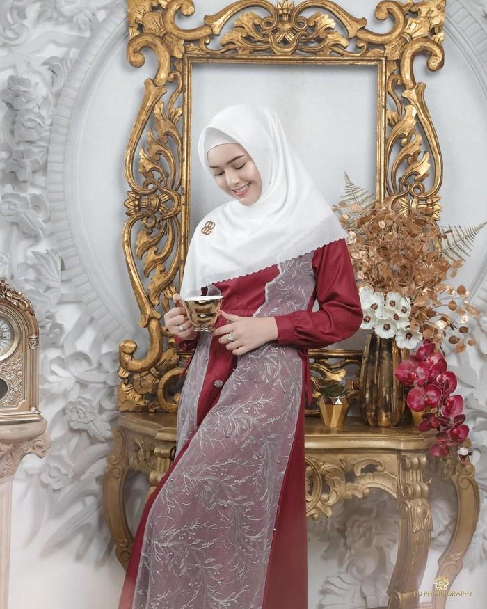 Dalam potret pertama, Amanda tampil memesona dalam balutan gamis berwarna merah dengan detail tulle outer warna putih. Senada dengan itu, hijab putih polos dengan laser cutting ditata menutup dada sehingga tampak lebih sopan. (Foto:instagram.com/fdphotography90)