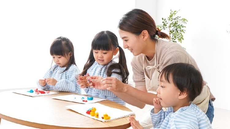 Asian kindergarten student girl with mother painting picture in book with color pencil at home, Homeschooling and distance learning.