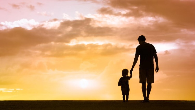 Loving father walking side by side with son holding hands.