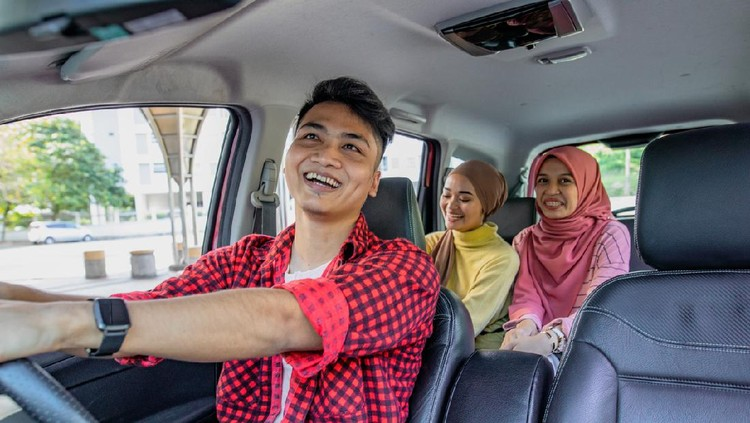 Three friend in the car. The driver is a male and looking to rear seat at mirror and smiling. The passenger is two asian hijab women smiling and laughing in the car