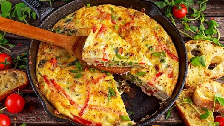 Frittata made of eggs, potato, bacon, paprika, parsley, green peas, onion, cheese in iron pan on wooden table