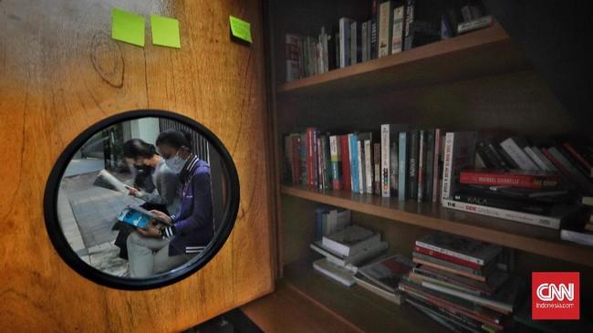 Para warga membaca buku di dekat perpustakaan bersama Bookhive Jakarta di kawasan Taman Situ Lembang, Jakarta, Selasa (27/4).