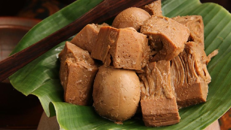 Close-up view of Gudeg, the signature dish of jackfruit stew from Jogjakarta. Chunks of jack fruit and eggs stewed with coconut milk, palm sugar, and teak leaves; commonly done in a traditional earthenware cooking jar known as kendil. Here shown the gudeg is arranged on a banana leaf that is placed on a kendil. A pair of wooden tongs is tucked on side further back.