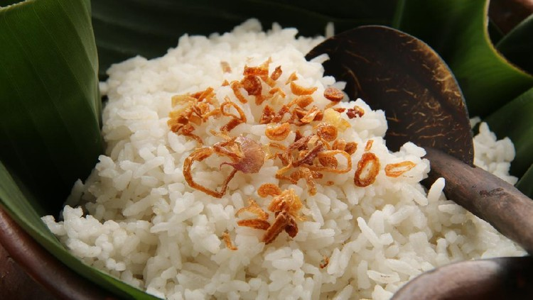 Nasi Uduk, savory rice dish from Betawi, Jakarta. It is steamed mixture of white rice and coconut milk. Commonly sprinkled with some fried shallots. The rice is placed on an earthenware pot lined with banana leaf, which in turn will add some leafy fragrant to the hot rice. A rice ladle made of coconut shell and wood is tucked among the rice grains.