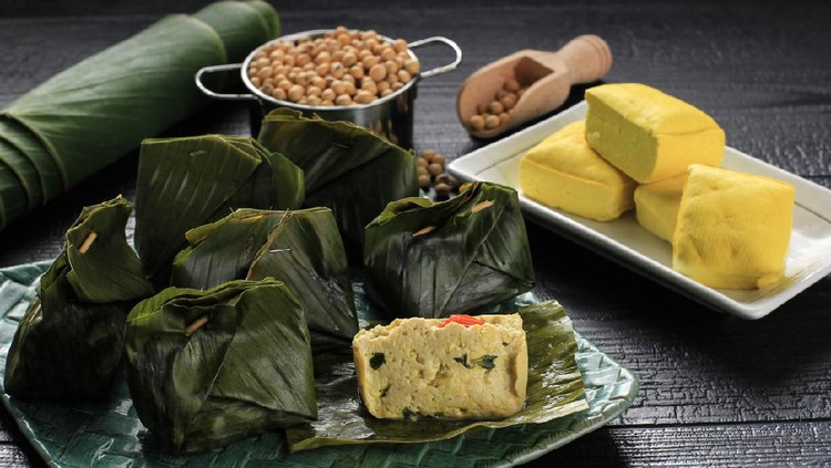 Pepes Tahu is Indonesian Spiced Tofu Wrapped with Banana Leaf and Steamed, Typically Indonesian Food from West Java (Sundanese). Steamed Tofu with Asian Basil. Served on Woven Plate, Black Background