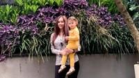 <p>Di kesempatan berbeda, Aura Kasih tampil <em>chic</em> memakai <em>blouse</em> yang dipadu bersama celana hitam. Ia menggendong sang putri yang memakai outfit kuning cerah. <em>So sweet</em>, Bunda! (Foto: Instagram @aurakasih)</p>