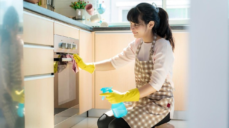 Asian woman wearing rubber protective gloves cleaning oven in her home during Staying at home using free time about their daily housekeeping routine.