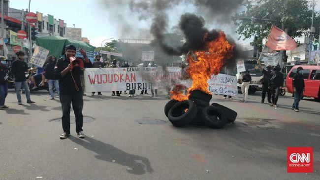 Buruh Makassar menuntut pencabutan UU Ciptaker dan pembayaran THR dalam demo dalam perayaan Hari Buruh Internasional 1 Mei 2021.