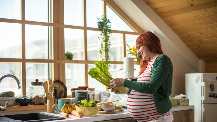 Pregnant redhead woman preparing healthy salad in bright kitchen