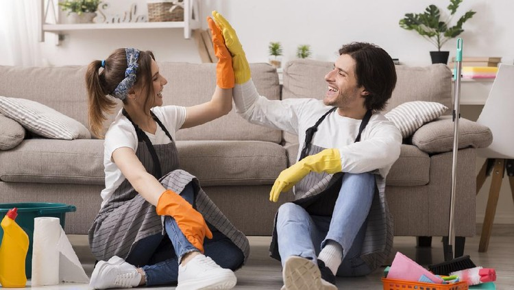 Housekeeping And Cleaning Service Concept. Happy Couple Giving High Five To Each Other After Spring-Clean In Apartment