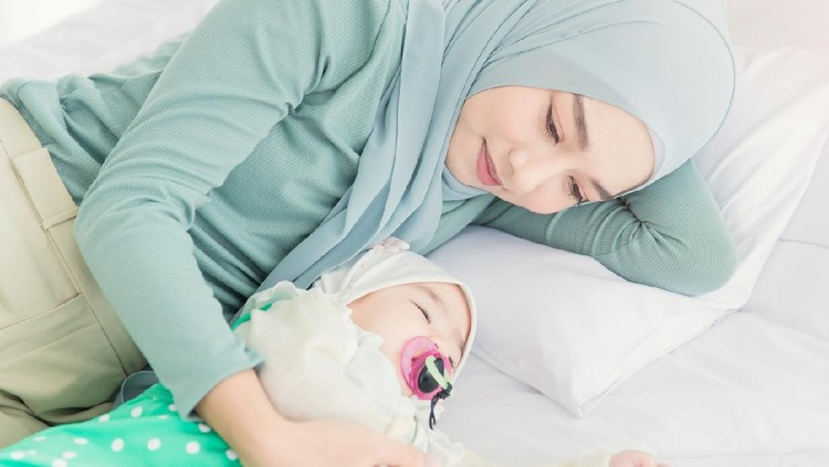 Happy muslim mother holding adorable little baby daughter wearing hijab in her arms on white bed in bedroom. Arab young mom wearing a head scarf, and she's sitting on the bed while holding her baby.
