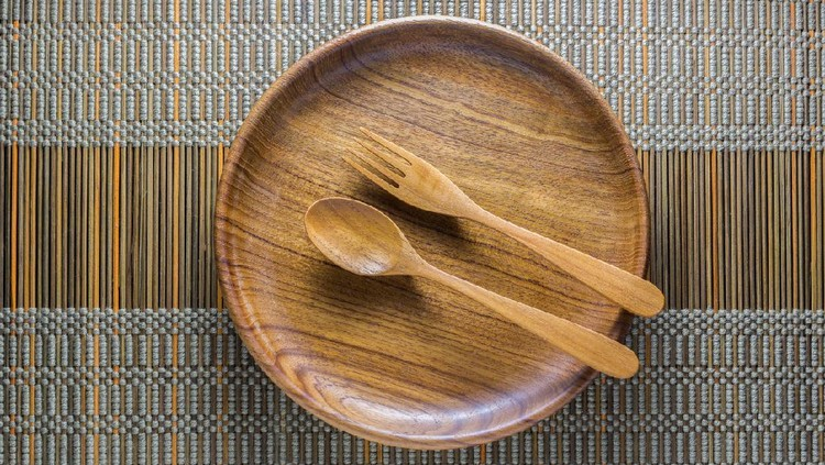 Dinning utensil set up on a green weaved bamboo mat