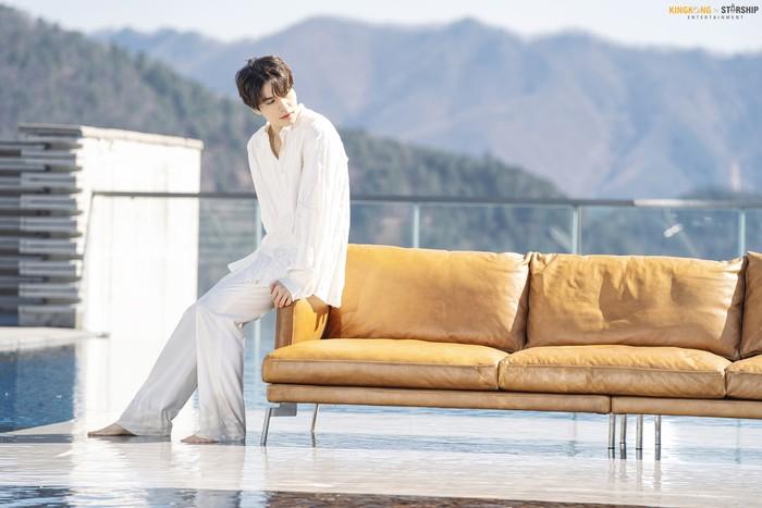 Meski mengenakan outfit polos serba putih, aktor kelahiran 6 November 1981 dengan zodiak Scorpio ini tetap memancarkan pesona yang menawan. Berlatarkan gunung, Lee Dong Wook duduk di ujung sofa coklat sambil menoleh ke arah kanan. (Foto: Naver.com/KINGKONG by Starship)