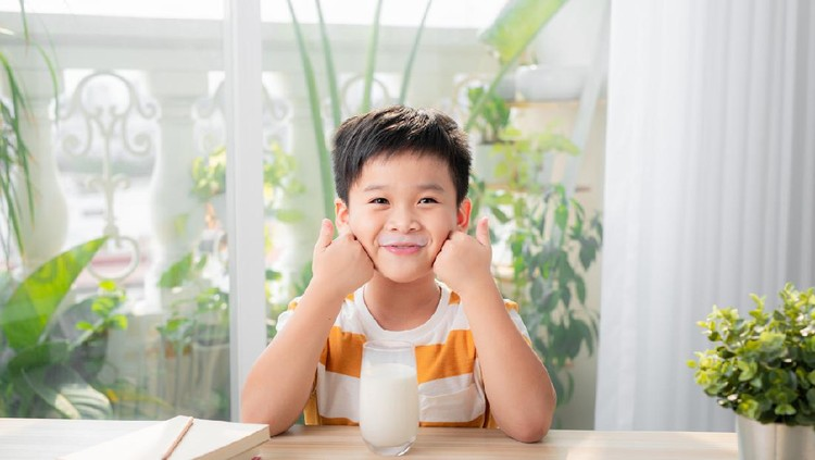 Adorable happy young Asian boy having breakfast and drinking milk at home in the morning; looking at camera