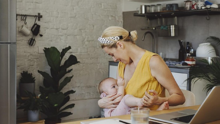 A portrait of a beautiful young Caucasian mother breastfeeding her adorable baby girl while working on a laptop in a kitchen at home.