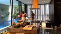 <p>Ketika masuk ke dalam rumah, tamu akan disambut dengan meja panjang di ruangan tengah yang dapat digunakan sebagai area tamu. Ada kolam renang yang dibatasi dengan jendela kaca untuk menambah suasana asri seperti berlbur di Bali. (Foto: YouTube NisNaz Channel)</p>