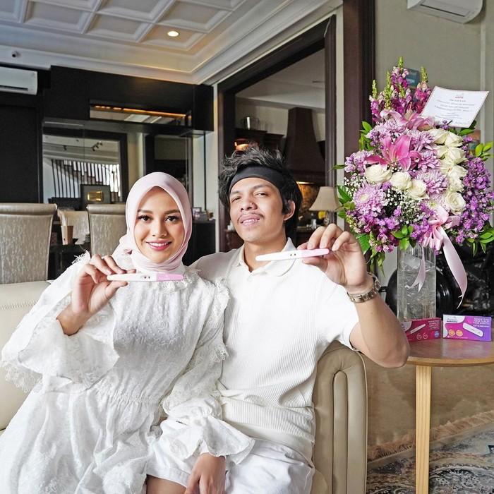 Mengumumkan kabar bahagia bersama sang suami tercinta, Aurel nampak begitu anggun dengan hijab berwarna putih senada dengan bawahan dan pakaian sang suami. (Foto: Instagram/aurelie.hermansyah)