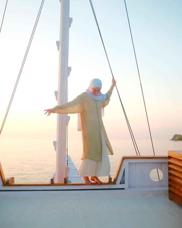 Agar rok putihmu enggak terkesan monoton, style dari Dinda Hauw bisa kamu contek, Ladies! Kenakan outer panjang berwarna cerah yang membuat tampilanmu di hari raya semakin segar. Pilih hijab yang senada dengan rokmu, ya. (foto: instagram.com/dindahw)