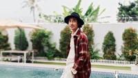 <p>Tak hanya tampan, Abidzar juga punya selera fashion yang sangat modis. Tengok saja gayanya ketika berpose di pinggir kolam memakai long plaid coat. (Foto: Instagram: @abidzar73)</p>