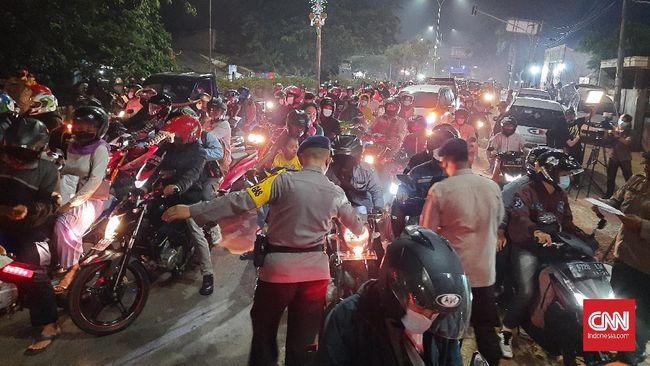 Puluhan pemudik bersepeda motor dipaksa putar balik oleh petugas kepolisian dan Satpol PP di pos penyekatan mudik di Kedungwaringin pada malam takbir.