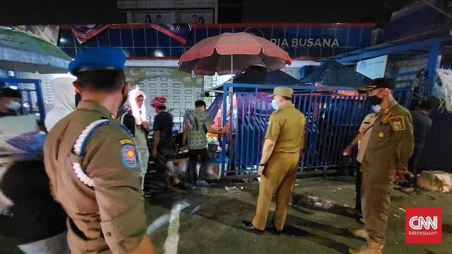 Aparat gabungan polisi, TNI, dan Satpol PP menutup paksa lapak pedagang di Pasar Jatinegara, Jakarta, demi mencegah kerumunan di malam takbiran, Kamis (13/5).