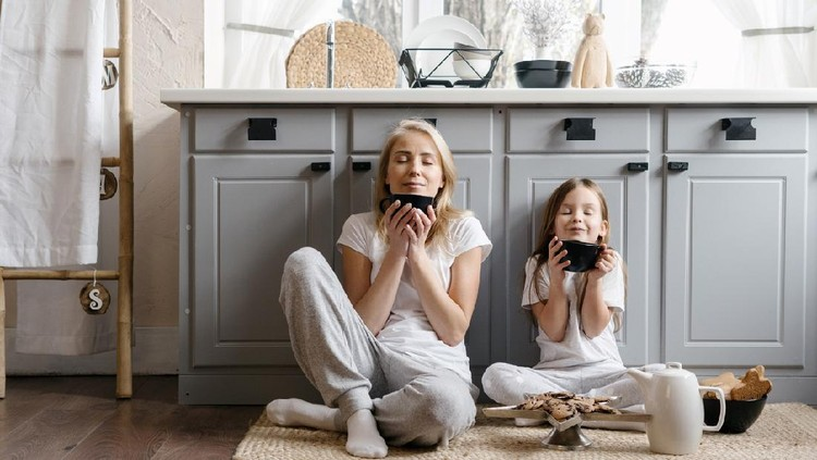 Dreamy mother sitting on kitchen floor together with her lovely daughter, enjoying morning coffee, drinking beverage and spending weekend in cozy apartment, resting at home