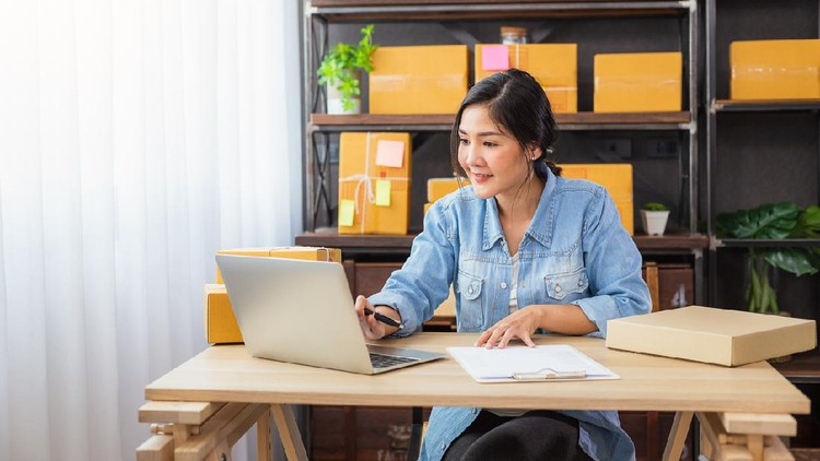 Young Asian female freelancer using her laptop and working at home, Small business female owner or Start up small business entrepreneur working online marketing packaging box delivery
