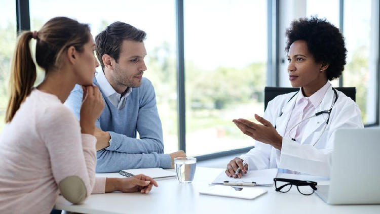 Black female doctor talking to a couple while having appointment at clinic.