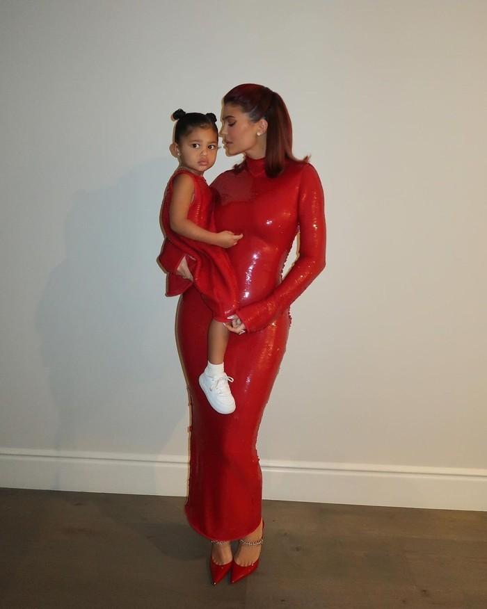 Saat perayaan Natal tahun lalu, Kylie dan Stormi mengenakan outfit bernuansa merah cerah. Meski berpotongan simple, namun material pakaian yang mengilap membuat outfit Natal mereka tetap terlihat mewah. (Foto: instagram.com/kyliejenner)