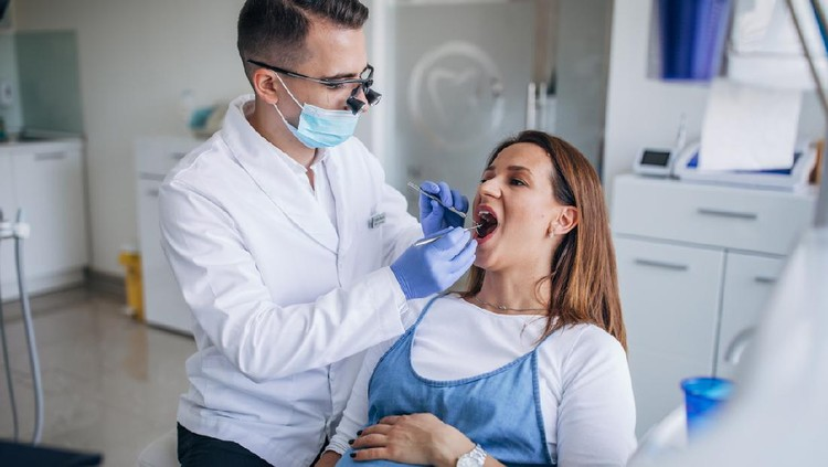 Man and woman, man dentist with a pregnant woman patient in ordination.