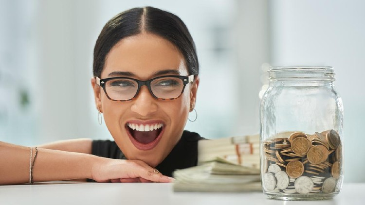 Cropped shot of an attractive young businesswoman looking excitedly over at a jar of coins and wads of cash in her office