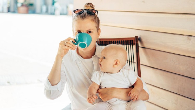 Caucasian young woman sits in a deck chair at the table, drinks coffee and holds the baby in her arms. Summer day in the city. Lifestyle portrait of mother with baby.