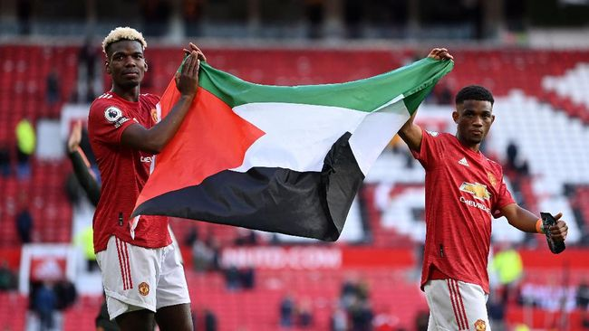 Penyerang PSV Eindhoven Eran Zahavi mengubah bendera Palestina yang dipegang gelandang Manchester United Paul Pogba dengan bendera Israel.