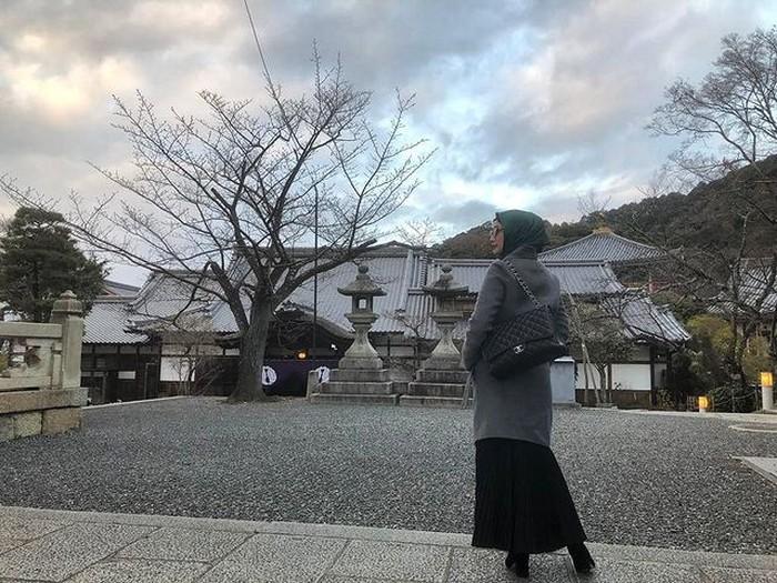 Saat liburan ke Kyoto, Jepang, Desy Ratnasari tampil sophisticated dengan coat dan maxi skirt berwarna monokrom. Agar tidak monoton, Desy menambahkan hijab berwarna hjau untuk look ini. (foto: instagram.com/desyratnasariterdepan)