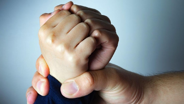 Father roughly holds the hands of his son. Child abuse, domestic violence. Concept image.