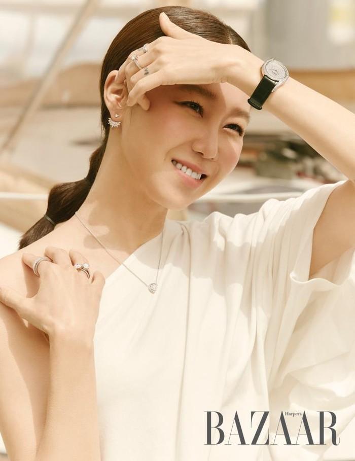 Pemakaian white half shouler blouse dengan perhiasan lengkap di jari-jemari, leher, lengan dan telinganya membuat penampilannya simple tapi tetap glamour/Sumber/Soompi.