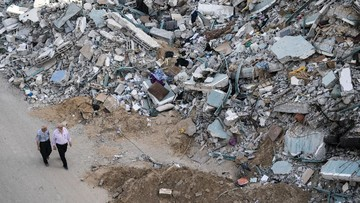People walk by the rubble of the al-Jalaa building following a cease-fire reached after an 11-day war between Gaza's Hamas rulers and Israel, in Gaza City, Friday, May 21, 2021. The building housed The Associated Press bureau in Gaza City for 15 years. (AP Photo/John Minchillo)