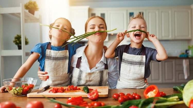mother with children preparing vegetable salad at home