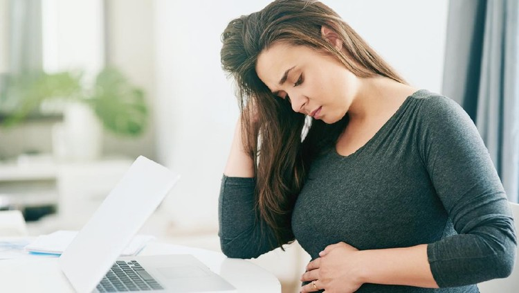 Shot of a young pregnant woman feeling unwell while working from home