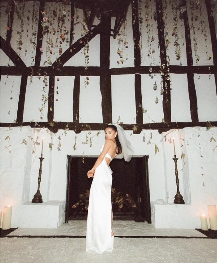 Pada pernikahannya, Ariana tampak cantik dan elegan dalam balutan gaun putih bermaterial satin karya desainer kenamaan Vera Wang. Penampilan Ariana yang simpel ini banyak menuai pujian dari fans dan netizen. (Foto: vogue.com/Stefan Kohli)