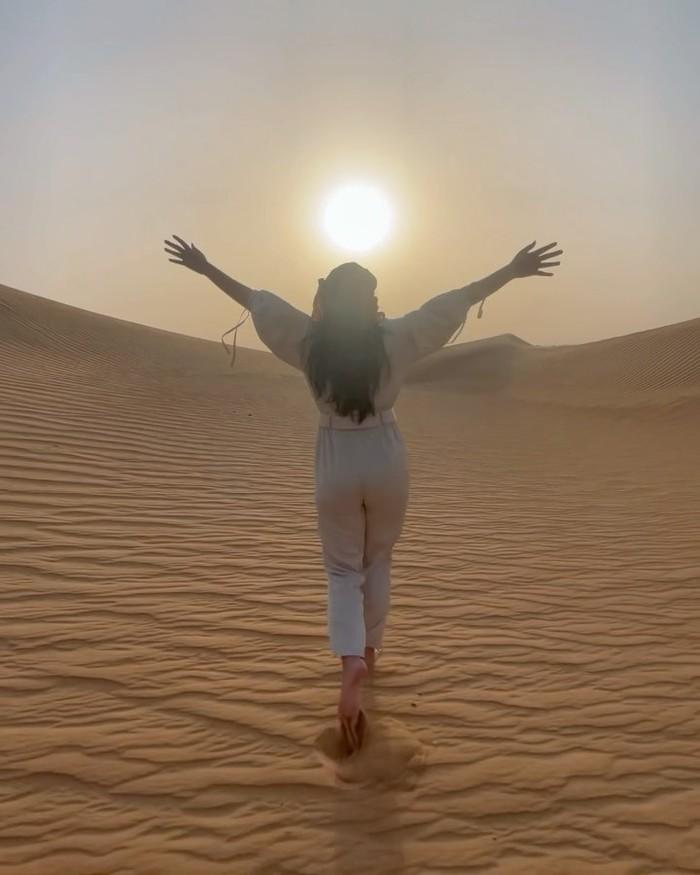 Pose menggapai matahari di tengah-tengah gurun seperti ini seakan menggambarkan suasana keceriaan yang tengah dirasakan Rachel. Dengan kedua tangan yang diangkat ke atas, aura bahagianya begitu terasa (Foto: instagram.com/rachelvennya)
