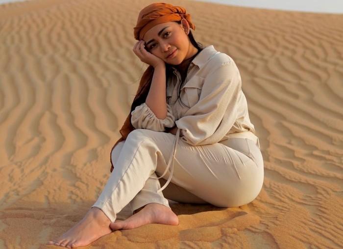 Saat berlibur, Rachel Vennya mengunjungi tempat-tempat ikonik di Dubai. Salah satunya adalah Desert Safari Dubai. Sambil duduk santai, Rachel tampak cantik dengan penutup kepala khas warga lokal di sana. (Foto: instagram.com/rachelvennya)