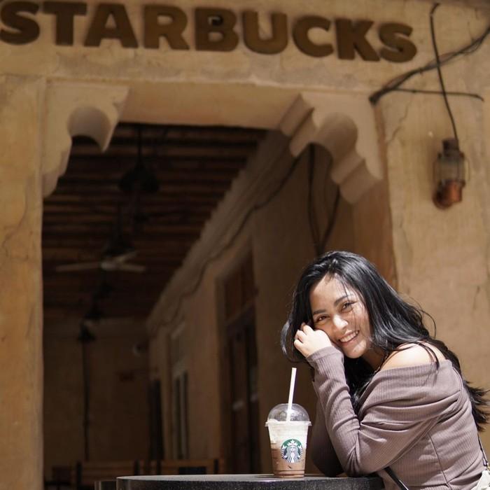 Senyum manis sumringah sembari menikmati minuman dingin seperti ini membuat pesona Rachel Vennya begitu memikat. Rambut hitam panjangnya dibiarkan tergerai ke arah belakang. (Foto: instagram.com/rachelvennya)