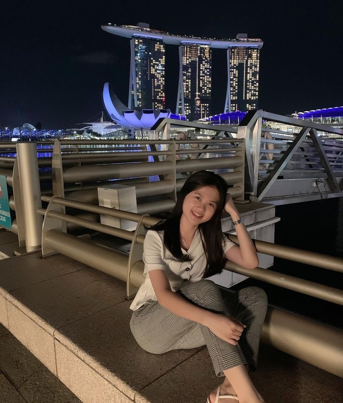 Sembari mengenakan blouse putih dan pants motif, Felicia tersenyum manis ke arah kamera. Pemandangan pun dipercantik dengan latar Marina Bay Sands di belakangnya. (Instagram.com/feliciatissue)