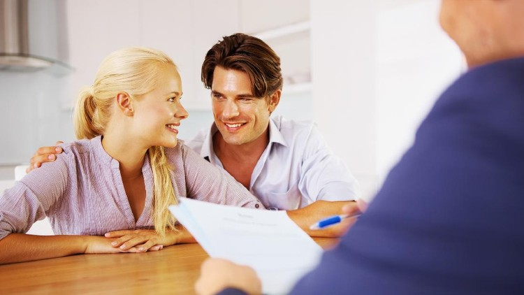 A young couple discussing their future at a table with their consultant