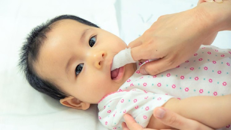 Mom brushes baby's teeth with a silicone brush that fits on her finger