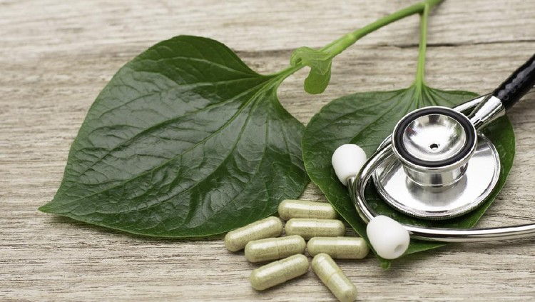 Betel Essential oil in bottle and green leaf on wooden table. Betel is a vine that has the heart shaped leaves.