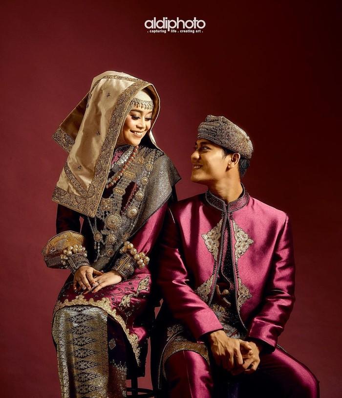 Kedua sejoli yang sering disebut Leslar ini nampak begitu bahagia dengan dalam pose busana Minang bernuansa ungu dan emas. Mereka berpose saling menatap satu sama lain sambil tersenyum bahagia. (Foto: Instagram.com/aldiphoto)
